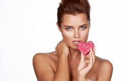 Beautiful sexy brunette woman eating cake shape of heart on a white background, healthy food, tasty, organic, romantic valentine d Royalty Free Stock Photos