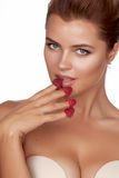 Beautiful sexy brunette woman eating raspberries on a white background, healthy food, tasty food, organic Royalty Free Stock Photography