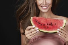 Beautiful sexy brunette woman eating watermelon on a white backg Royalty Free Stock Photo