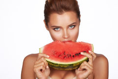 Beautiful brunette woman eating watermelon on a white background, healthy food, tasty food, organic Stock Photos