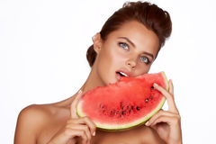 Beautiful sexy brunette woman eating watermelon on a white background, healthy food, tasty food, organic Stock Image