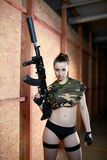 Beautiful sexy brunette woman holding army weapon Royalty Free Stock Image