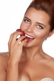 Beautiful brunette woman holding four berries on her fingers, smiling and is going to eat raspberries on a white backgro Royalty Free Stock Images