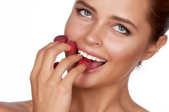 Beautiful brunette woman holding four berries on her fingers, smiling and is going to eat raspberries on a white backgro Royalty Free Stock Photo