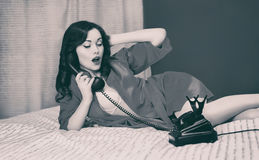 Beautiful sexy brunette woman lying on bed talking on the vintage telephone, retro black white film photo Royalty Free Stock Photo