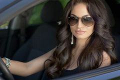 Beautiful brunette woman model with sunglasses sitting in a Stock Photography