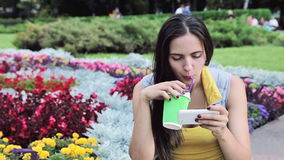 Beautiful sexy brunette woman waiting in the park drink coffee play in smartphone call phone smile flower summer good weather chec stock footage