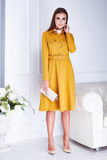 Beautiful sexy brunette woman wear elegant fashion yellow. Dress hold small bag high heels clothes for date meeting summer collection model in white room Stock Photos
