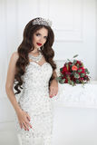 Beautiful sexy brunette young woman with red lips makeup and lon. G wavy hair style, lady wears in red dress lying on modern sofa in white interior Stock Photos