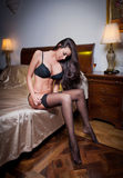 Beautiful and sexy brunette young woman wearing black lingerie in bed. Fashion shoot lingerie indoor. Sexy young girl in black Stock Photography