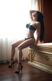 Beautiful sexy brunette young woman wearing black lingerie sitting on bed in window light. Fashionable female with attractive body Stock Photos