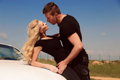 Beautiful sexy couple in casual  clothes posing beside auto Stock Images