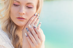 Beautiful sexy cute gentle blonde girl in a white dress holding hands near the face with long acrylic nails Stock Images