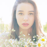 Beautiful cute girl with big lips and red lipstick with bared shoulders with a bouquet of daisies at sunset on a sunny warm Royalty Free Stock Photo