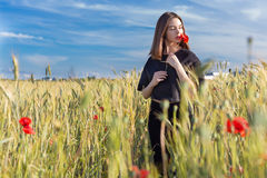 Beautiful sexy cute girl with big lips and red lipstick in a black jacket with a flower poppy standing in a poppy field at sunset Stock Image