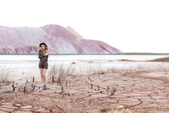 Beautiful sexy cute girl in a fashion shot wearing a hat and overalls in the desert with dry cracked ground on a mountains Stock Photography