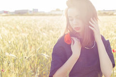 Beautiful sexy cute girl holding poppy flowers in his hands at sunset on a sunny summer day Royalty Free Stock Photos
