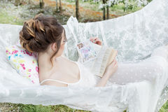 Beautiful cute girl in a light white dress in apple blossoming garden sees on the hammock with a book stock photo