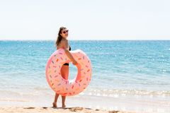 Beautiful sexy cute happy woman running on the beach with a pink rubber inflatable ring in the hand. Summer holidays and vacation royalty free stock photos