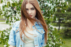 Beautiful cute sweet girl with long red hair and green eyes in a denim jacket near a flowering tree in the park the wind. Blowing her hair stock images
