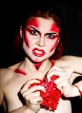 Beautiful sexy devil girl with professional make-up. Fashion Art design. Attractive woman bites the heart Stock Photography