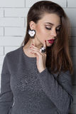 Beautiful elegant fashionable woman with bright evening make-up with big lips plump demonstrates Handmade Jewelry in fashiona Royalty Free Stock Photography