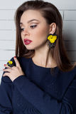 Beautiful sexy elegant fashionable woman with bright evening make-up with big lips plump demonstrates Handmade Jewelry in fashiona Stock Photography