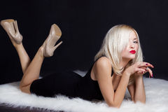 Beautiful sexy elegant striking blonde woman with bright makeup red lips in a black dress lies on the white fur in Studio Stock Image