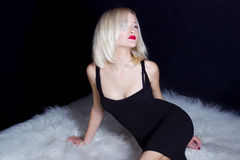 Beautiful sexy elegant striking blonde woman with bright makeup red lips in a black dress lies on the white fur in Studio Stock Photography