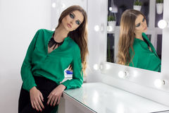 Beautiful sexy elegant woman with bright evening make-up in shades of green with long hair in a green evening dress in a festive Stock Photos