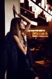 Beautiful fashion brunette woman in expensive interior restaurant. On dark cafe background stock photo