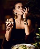Beautiful sexy fashion brunette woman in expensive interior restaurant eat oyster and lick one finger. On dark cafe background Royalty Free Stock Photo