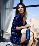 Beautiful fashion brunette woman sitting in expensive interior restaurant bottle of blue margarita cocktail. Looking at the corner royalty free stock image