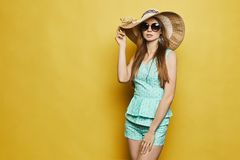 Beautiful, sexy, fashionable blond girl in shorts, hat and sunglasses posing at yellow background stock photo