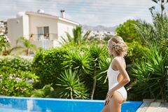 Beautiful, sexy and fashionable blonde model girl in swimsuit with sporty shape posing in swimming pool.  Royalty Free Stock Photos