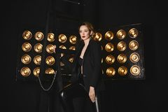 Beautiful, sexy, fashionable half-naked blonde girl in a black jacket and leggings posing with studio lamps on a background.  Royalty Free Stock Images
