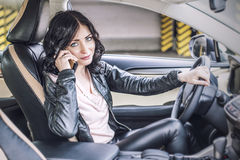 Beautiful sexy female model in leather clothes with a white car Stock Images