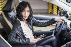 Beautiful female model in leather clothes with a white car royalty free stock images