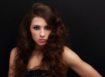Beautiful sexy female model with long curly hair looking vamp on black Stock Photo