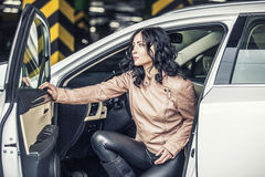Beautiful sexy female model with a white car in the Parking lot Stock Images
