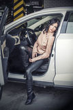 Beautiful sexy female model with a white car in the Parking lot Royalty Free Stock Images
