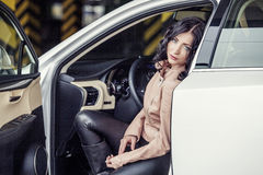 Beautiful sexy female model with a white car in the Parking lot Stock Photography