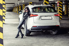 Beautiful sexy female model with a white car in the Parking lot Stock Photo