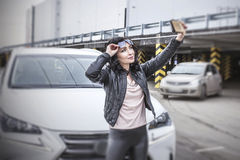 Beautiful sexy female model with a white car and a smartphone ma Royalty Free Stock Photos