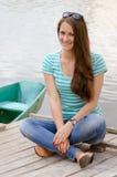 Beautiful sexy female wearing sailor striped dress sitting near boat Stock Photos