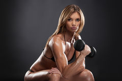 Beautiful sexy fit woman doing exercise for biceps. Royalty Free Stock Photography