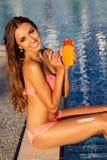 Beautiful sexy girl applying sunscreen lotion on her legs Stock Photo