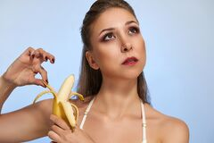 Beautiful sexy girl with banana isolated on light studio background. Fashion food photography