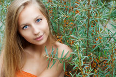 Beautiful sexy girl with big lips long hair with dark skin sits near sea buckthorn summer on a warm Sunny day Stock Images