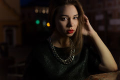 Beautiful sexy girl with big lips with red lipstick on a city street at night near the lantern Stock Images